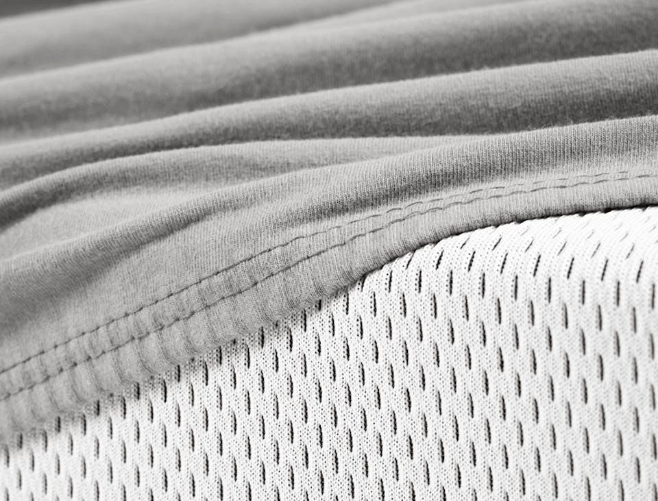 Foto in Nahaufnahme: Die BODYGUARD Matratze ist halb mit dem BODYGUARD Spannbettlaken bezogen. Die hohe Auflösung zeigt die geschmeidige Struktur und den dicken Stoff des Spannbettlaken.