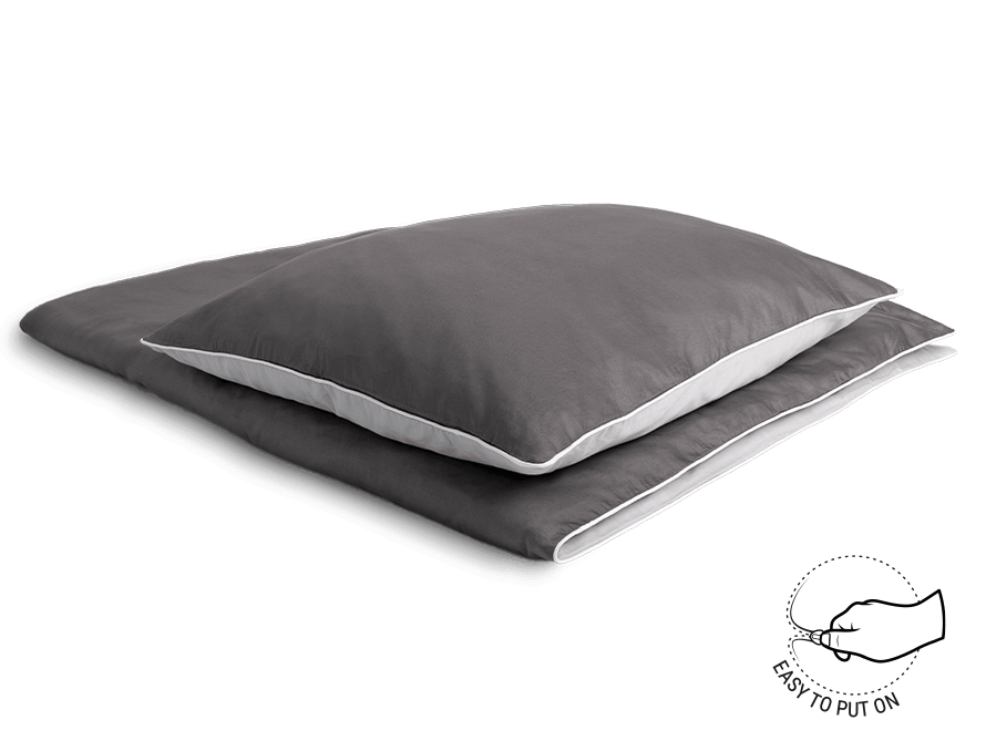 Photo: A folded bedspread covered with BODYGUARD Satin Bed Linen. On it a matching pillow. The symbol next to it shows a zipper, which says: easy to put on.