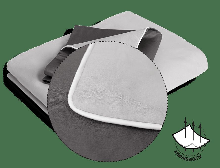 Foto: Eine zusammengelegte Bettdecke bezogen mit der BODYGUARD Satin-Bettwäsche. Eine Ecke ist umgeklappt, so dass die unterschiedlichen Farbseiten erkennbar sind. Das Symbol daneben zeigt: Atmungsaktiv.