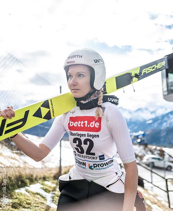 Foto: Eine Skispringerin schultert ihre Skier; auf ihrem Trikot Werbung für bett1.