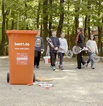 Foto: Im Vordergrund eine rote Tonne, im Hintergrund Kinder mit Tennisschlägern.