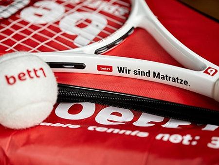 """Foto: Im Fokus der Hals eines Tennisschlägers mit der Aufschrift """"bett1 – Wir sind Matratze.""""; unscharf davor liegt weißer bett1-Tennisball."""