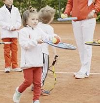 Foto: Drei Kinder und ein Erwachsener jonglieren einen Tennisball auf einem Tennisschläger.