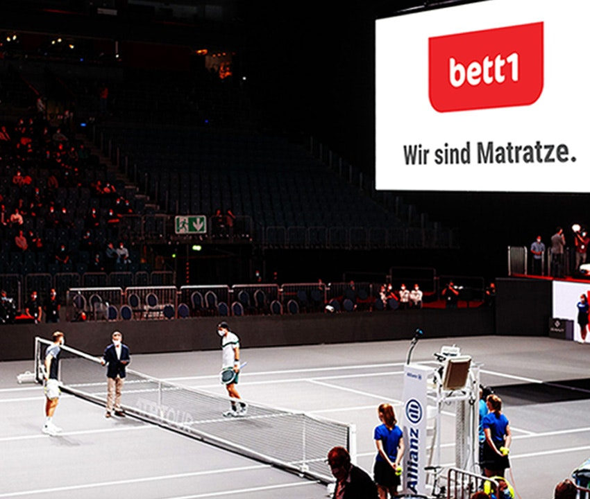 """Foto: Bei den bett1HULKS stehen sich zwei Spieler an Netz gegenüber, die Leuchttafel in der Arena zeigt den bett-Slogan """"Wir sind Matratze.""""."""