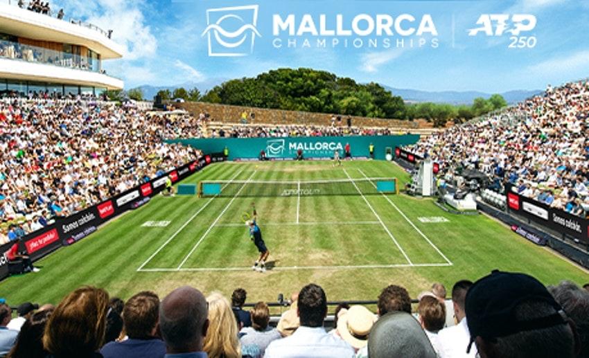 """Foto: In einem gefüllten Stadion läuft ein Tennis-Match auf Rasen; darüber der Schriftzug """"Mallorca Championships""""."""