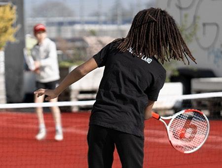 Foto: Ein Kind spielt einen roten Tennisball über das Netz zu einem anderen Kind.