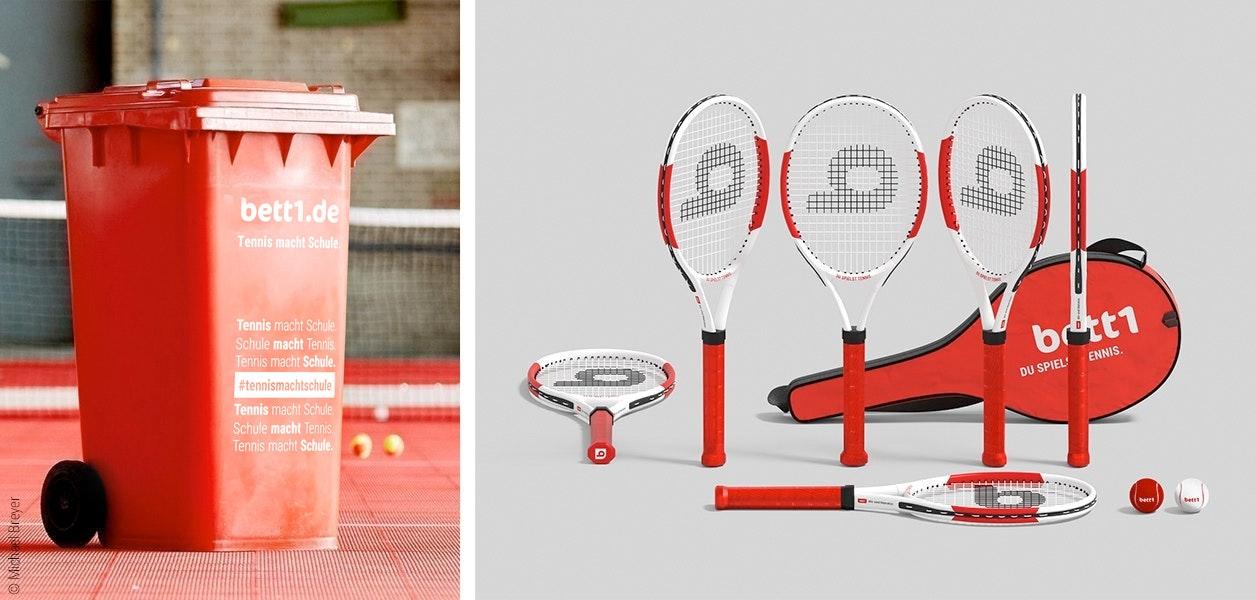 """Foto: Links eine rote Tonne mit der Aufschrift """"bett1.de – Tennis macht Schule""""; rechts mehrere Tennischläger, eine Schlägertasche mit der Aufschrift """"bett1.de – Du spielst Tennis."""" und je ein roter und weißer Tennisball."""