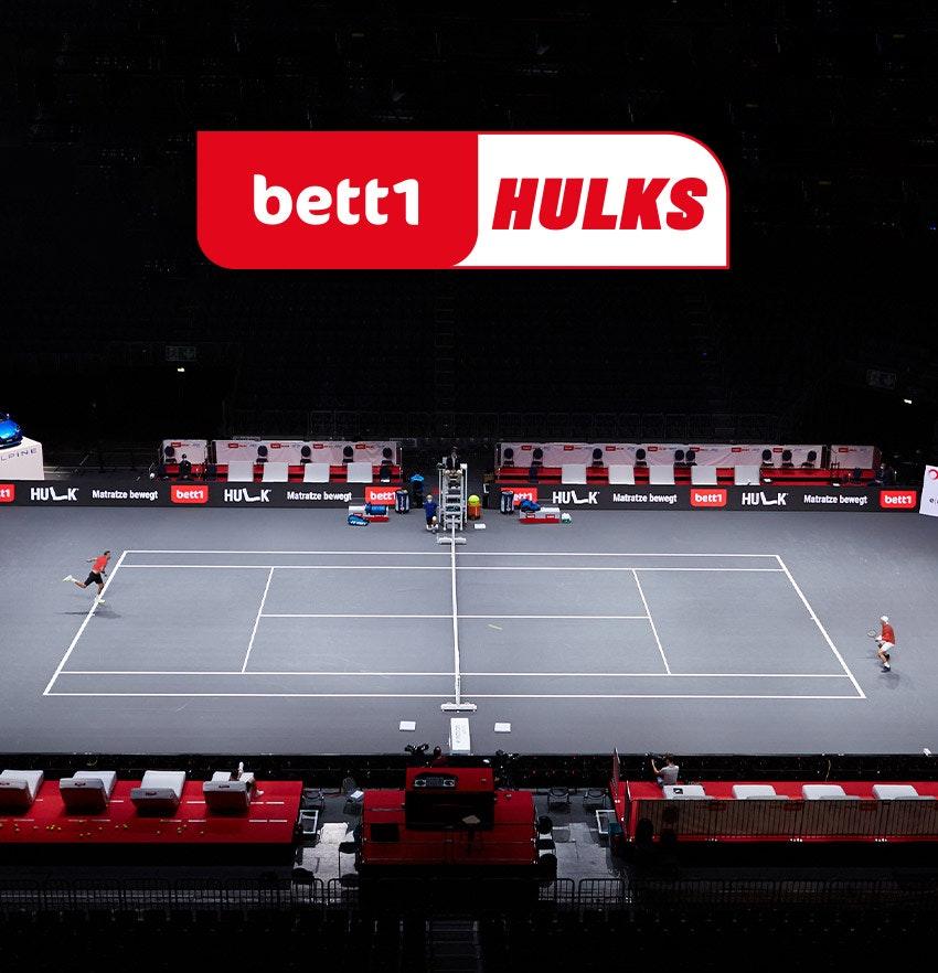 Foto: Eine Spielszene des Tennisturniers bett1HULKS darüber das Logo der bett1HULKS.