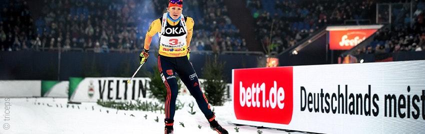 Foto: Eine Skilangläuferin; im Hintergrund eine Bandenwerbung von bett1.