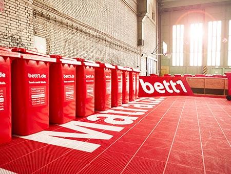 Foto: Eine Reihe von roten bett1-Tonnen auf einem roten Hallentennisplatz.