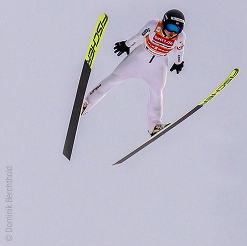 Foto: Eine Skispringerin in der Luft; auf ihrem Trikot Werbung für bett1.