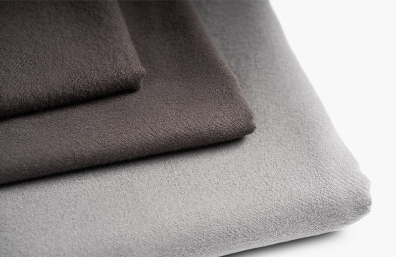 Photo: A stack of folded BODYGUARD Flannel Bed Linen. At the bottom there is a duvet cover with the silver side facing outwards, on top there are two pillowcases with the anthracite side.