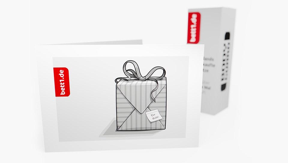 Der bett1.de Geschenkgutschein mit Geschenkpaketmotiv, im Hintergrund der Bodyguard Karton im Mini-Format