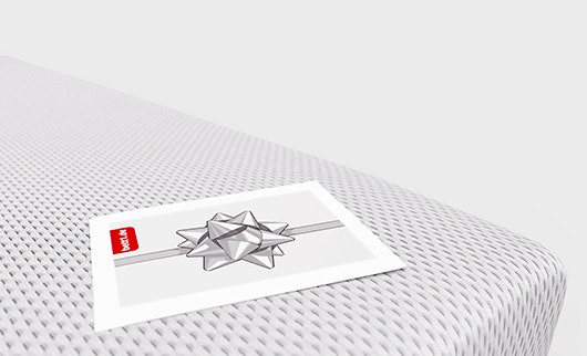 Der bett1.de Geschenkgutschein mit Schleifenmotiv liegt auf der Bodyguard Matratze